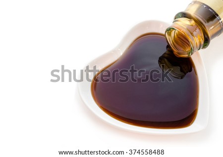 Oyster sauce in white cup heart shape on white background. - stock photo