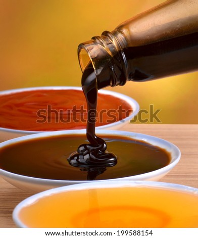 Oyster sauce poured out from the bottle   - stock photo