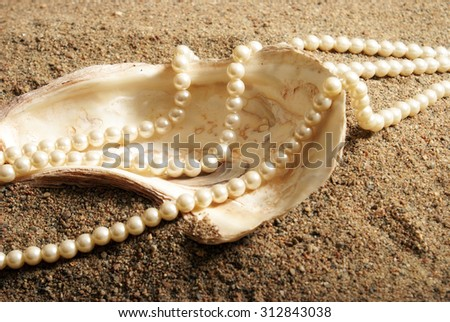 Oyster shell with pearls on a sandy beach.             - stock photo