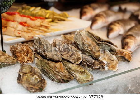 Oysters and fish on iced market display - stock photo