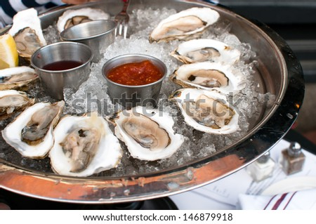 Oysters served raw with sauces and lemon - stock photo