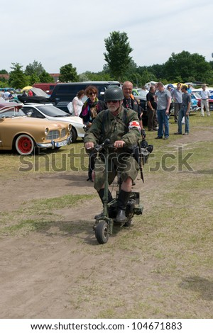 "PAAREN IM GLIEN, GERMANY - MAY 26: A military medic on Motorized scooter, ""The oldtimer show"" in MAFZ, May 26, 2012 in Paaren im Glien, Germany"
