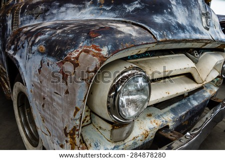 PAAREN IM GLIEN, GERMANY - MAY 23, 2015: Fragment of rusted body of full-size pickup truck Ford F100. The oldtimer show in MAFZ. - stock photo
