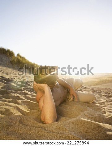 Pacific Islander man laying in sand - stock photo
