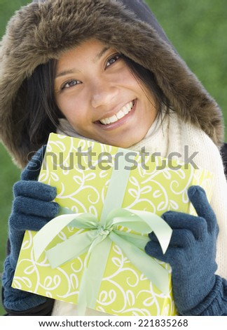 Pacific Islander woman holding gift - stock photo