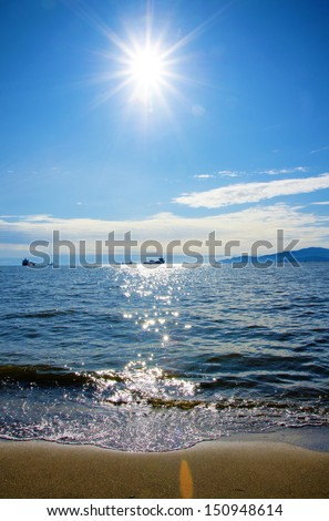 Pacific Northwest ocean beach near Vancouver English Bay with sun at noon midpoint - stock photo