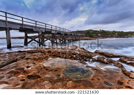 pacific ocean bare island near Sydney, La Perouse at sunrise with wooden bridge connecting with mainland and bottom uncovered after sea water tiding away - stock photo