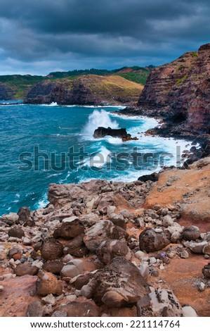 Pacific Ocean waves hitting the tall rocky cliff coastline created from lava on Maui, Hawaii, USA - stock photo