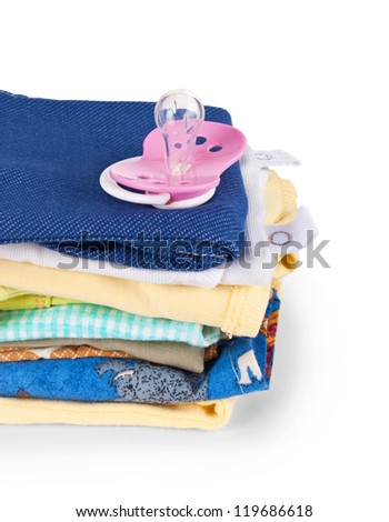 Pacifier and a pile of baby clothes, isolated on white - stock photo