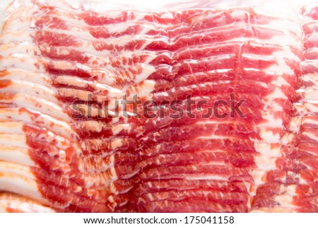Pack of Bacon Sealed in Clear Plastic on White Table - stock photo