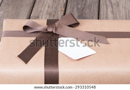 Package wrapped in brown paper with ribbon and bow - stock photo