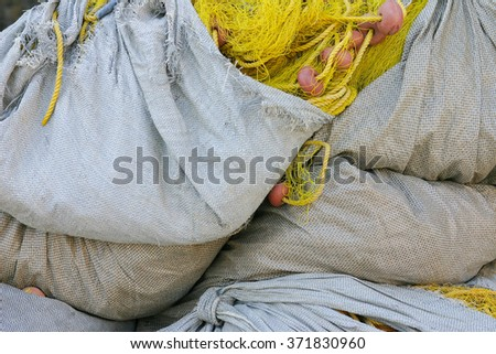 Packages fishing nets on the pier in the harbor - stock photo