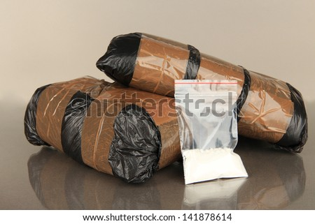 Packages of  narcotics on gray background - stock photo