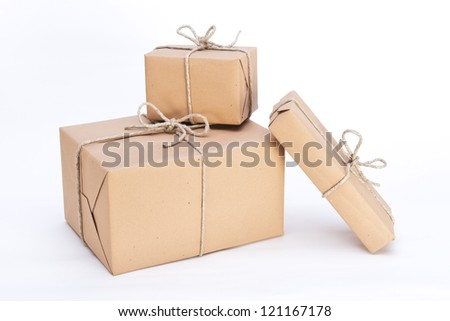 packages ready for shipment, wrapped in brown paper and tied with string - stock photo