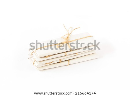packages wrapped with brown kraft paper and tied with twine isolated on white background with shadow - stock photo
