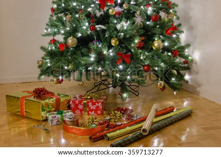 Packed presents and decorative wrapping paper in evening lights of Christmas Pine Tree. Classic colors: red, green and golden yellow.