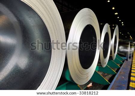 packed rolls of steel sheet in a warehouse - stock photo
