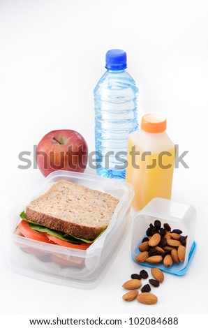 Packed sandwich, apple, orange juice, dried fruit and nuts with a bottle of water isolated on white - stock photo