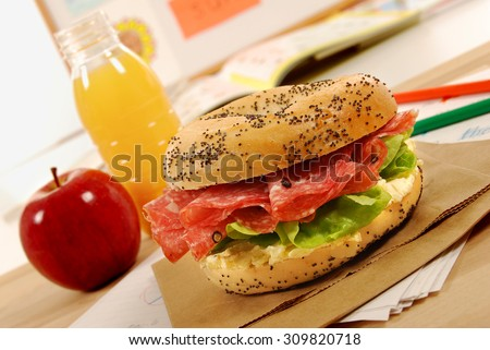 Packed school lunch: salami bagel sandwich with apple and drink in classroom