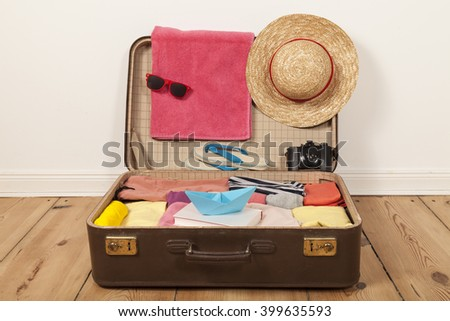 Packed suitcase with sun glasses and beach hat