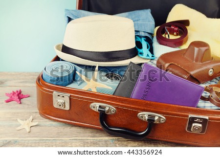 Packed vintage suitcase for summer holidays, vacation, travel and trip. Retro toning. - stock photo