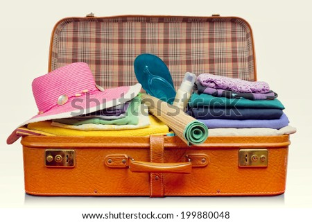 Packed vintage suitcase full of vacation items.