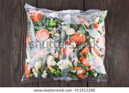 Packet of frozen vegetables on a old wooden table, top view - stock photo