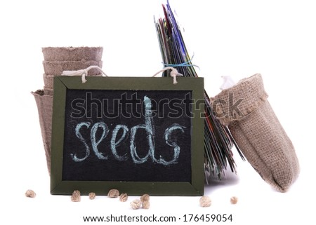 """packets of seeds, peat pots and a wooden plaque with the inscription """"seeds"""" on a white background  - stock photo"""