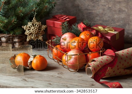 Packing Christmas gifts and tangerines with apples