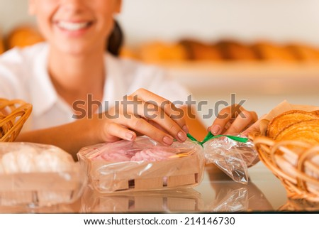 Packing cookies for sale. Beautiful young woman in apron packing cookies and smiling while standing in bakery shop - stock photo