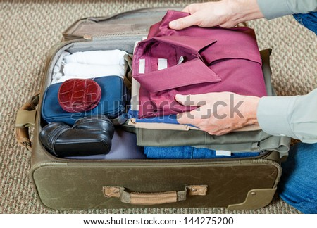 Packing suitcase - stock photo