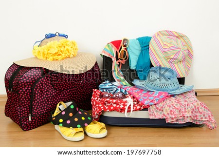 Packing the suitcase for summer vacation. Full luggage and bags with summer clothes,hats and accessories. - stock photo