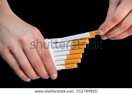 Packs of cigarettes and hand isolated on black background - stock photo