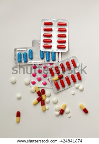 packs of colorful pills in blisters and a lot of scattered pills and capsules around - stock photo