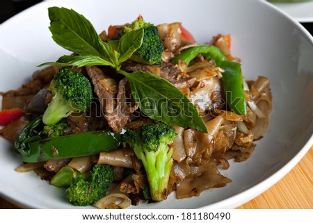 Pad kee mao drunken noodle thai dish closeup with beef and mixed vegetables. - stock photo