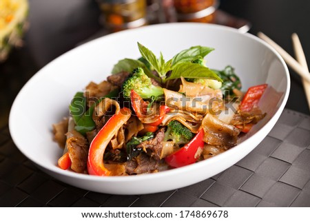Pad kee mao drunken noodle thai disk with beef and mixed vegetables. - stock photo