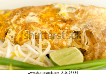 Pad Thai ( Stir Fried Rice Noodle in Thai tradition style  )  wrap with omelet and lemon closeup - stock photo