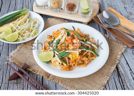 Pad Thai with garnish on wooden dinning table, Thai food rustic style - stock photo