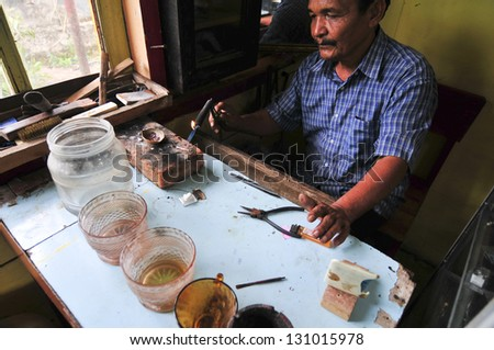 PADANG, INDONESIA - APRIL 27: Unidentified Indonesian Jeweler forming silver as he makes jewelry. Mining and refining minerals and Jewels is one of Indonesia biggest industries. April 27 2011, Padang, Indonesia - stock photo