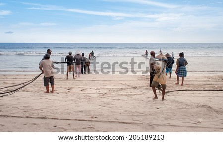 PADANG, INDONESIA - DEC 25, 2013: Fishermen on Tiku beach. Fishing is the main work in some villages. Fishermen pulling a fishing net about two hours