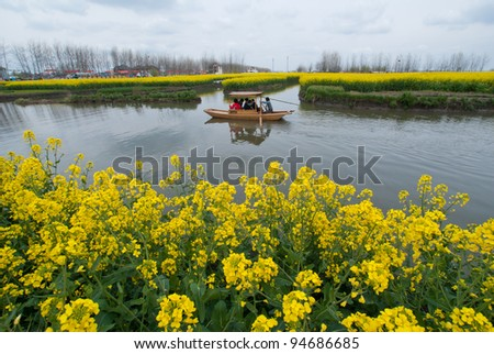 Paddle Boat along canal in Rapeseed field, Xinghua China - stock photo