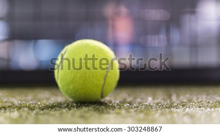 Paddle tennis ball in court with night ambient light and narrow deep of field.