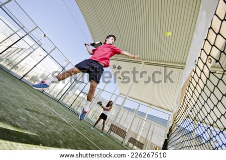 Paddle tennis couple playing in outdoors court. Wide angle image. Man hits ball. - stock photo