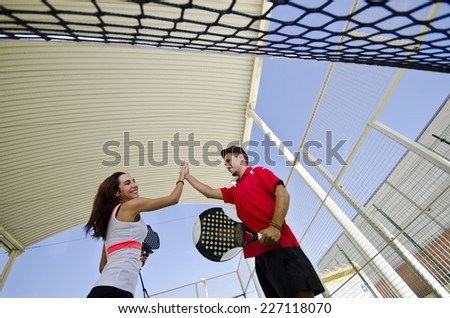Paddle tennis couple team fair play in outdoors court - stock photo