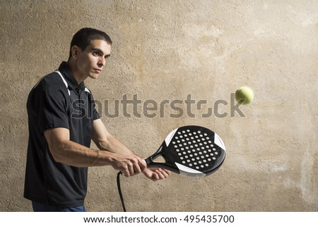 Paddle tennis player playing on concrete wall