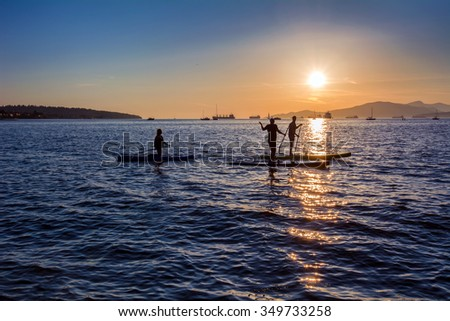 Paddleboarding on a summer day and awesome mountains - stock photo
