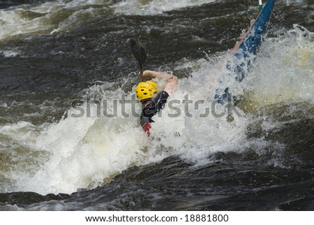 Paddler, overcoming a difficult obstacle in the rough whitewater river.