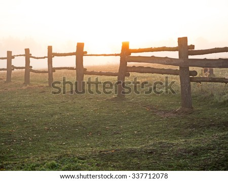 Paddock fence at sunrise on an autumn day - stock photo