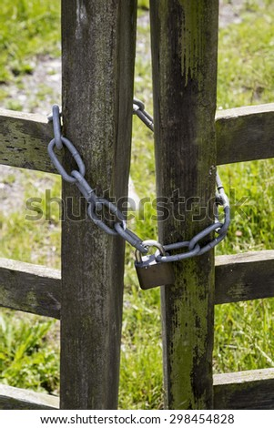 Padlock and chain attached to wooden farm Gate - stock photo