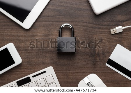 padlock and different gadgets on the wooden office table. privacy protection, encrypted connection concept, buying online